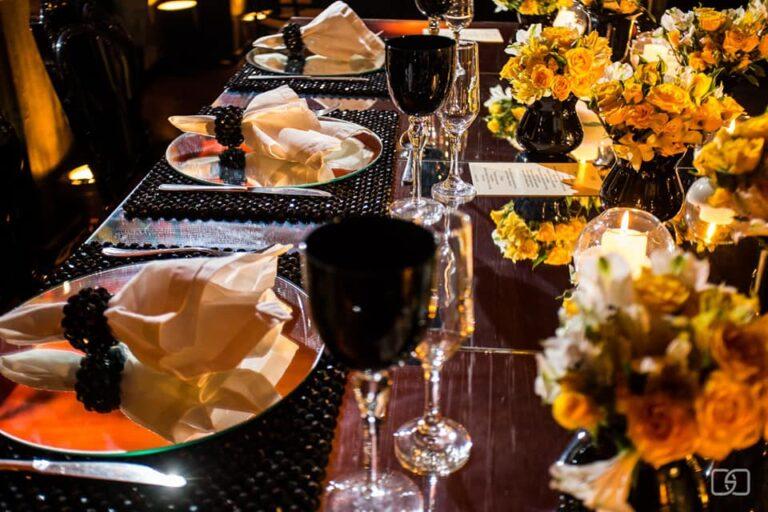 mesa-espelhada-jantar-formandos-tacas-pretas-flores-amarelas-guardanapos-brancos