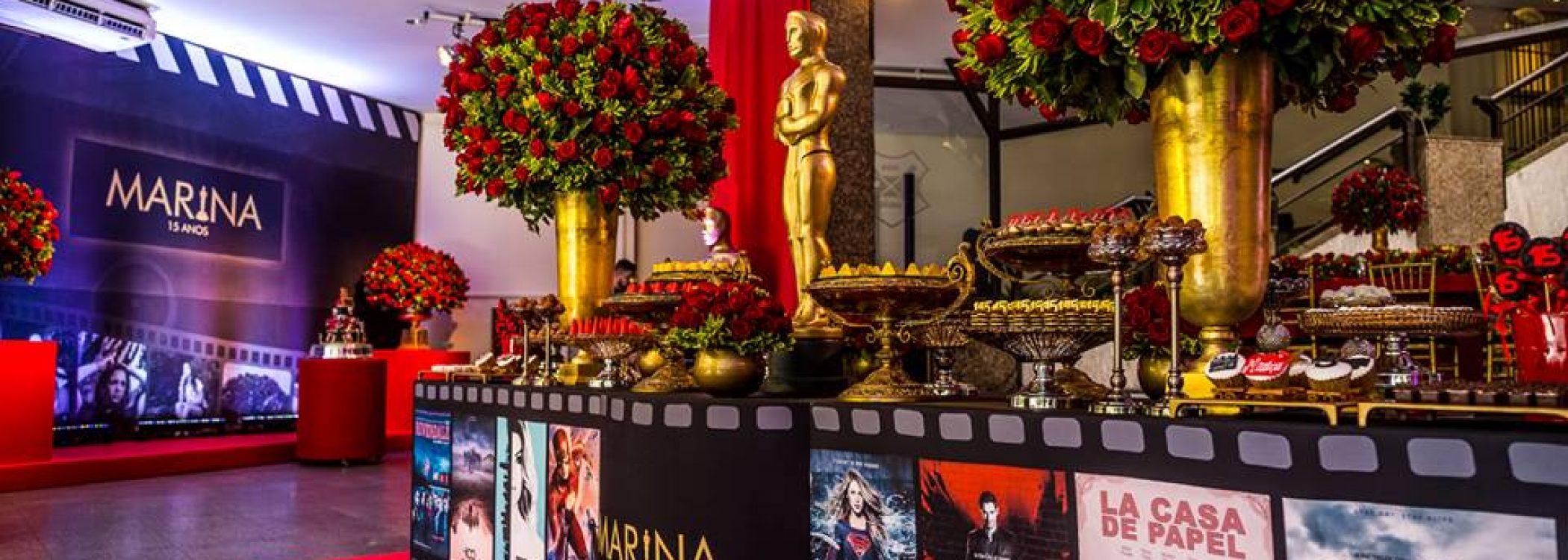 mesa-de-doces-forrada-com-filmes-e-series-arranjos-vasos-dourados-flores-vermelhas-tapete-vermelho-festa-tematica-oscar